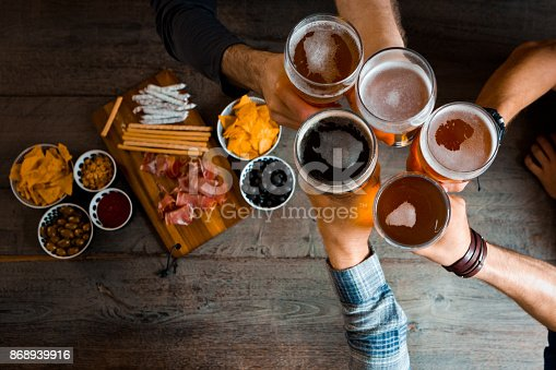 istock Top view of friends toasting with beer glasses in the pub 868939916