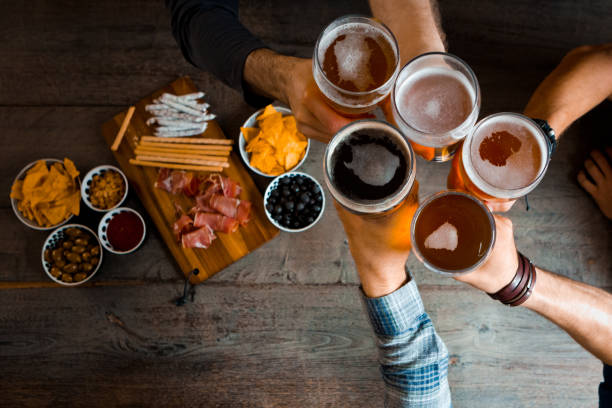 top view of friends toasting with beer glasses in the pub - happy hour stock photos and pictures