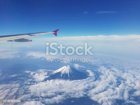istock Top view of fuji mountain and wing of the air plane from window airplane with an Aerial view background, Yamanashi, Japan 1018393134
