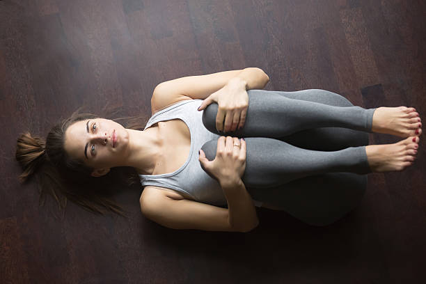 Top view of Gas Release yoga posture Beautiful young woman working out at home, doing yoga exercise for spine on wood floor, lying in Knees to Chest pose, Pawanmuktasana, Gas Release Posture, resting after practice. Full length, top view apanasana stock pictures, royalty-free photos & images