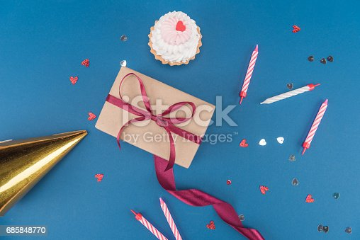 istock top view of gift box, cake, candles and birthday hat isolated on blue, birthday party concept 685848770