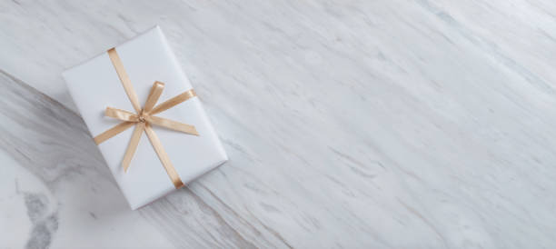 Top view of gift box with gold ribbon on white marble background. stock photo