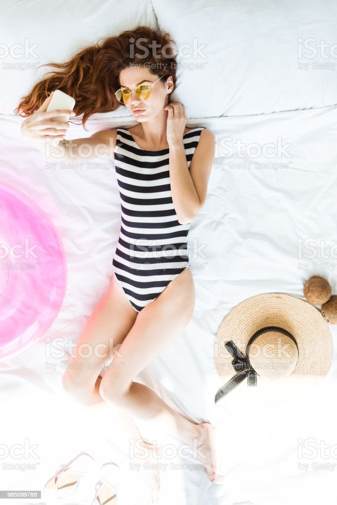 Top view of girl in swimsuit taking selfie on bed among travel objects royalty-free stock photo