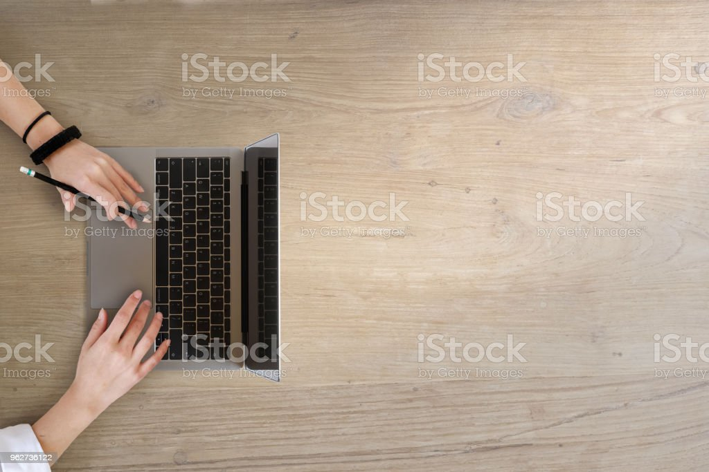 Top view of girl's hands using laptop on a wooden table with copy space. - Foto stock royalty-free di Adulto
