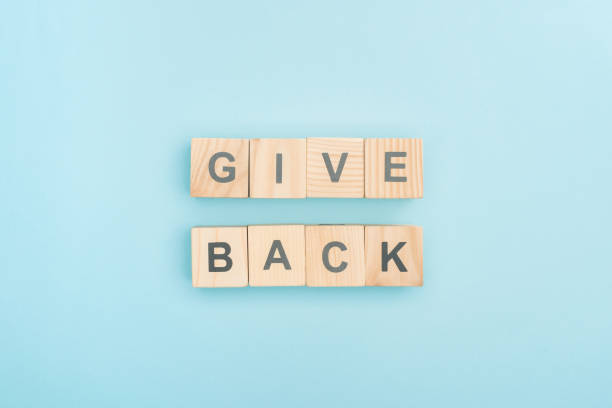 top view of give back lettering made of wooden cubes on blue background stock photo