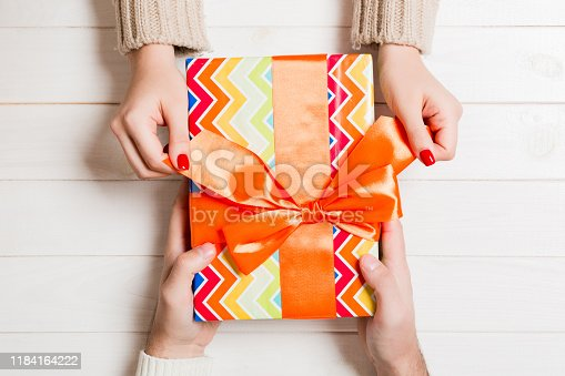1125461272 istock photo Top view of giving and receiving a present on wooden background. A man and a woman holding gift in hands. Close up of festive concept 1184164222