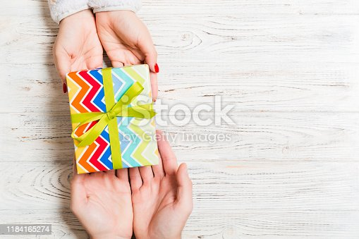 1125461272 istock photo Top view of giving and receiving a present on wooden background. A man and a woman holding gift in hands. Festive concept with copy space 1184165274