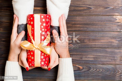 1125461272 istock photo Top view of giving and receiving a present on wooden background. A man and a woman holding gift in hands. Festive concept with copy space 1186056780