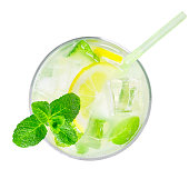 top view of glass of cold lemonade with slices of lemon, leaves of mint, cubes of ice and straw isolated on white background