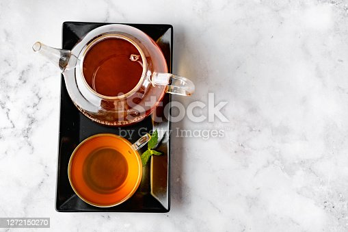 Top view of glass tea cup and glass kettle on black tray and white marble backround. Copy space. Tea concept