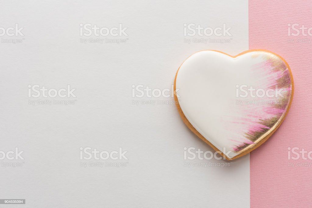 top view of glazed heart shaped cookie on pink surface stock photo