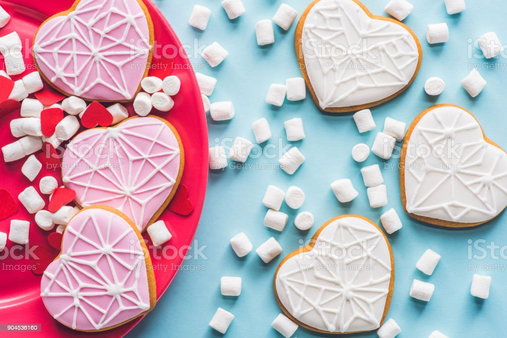 top view of glazed heart shaped cookies on pink plate with white marshmallow isolated on blue stock photo