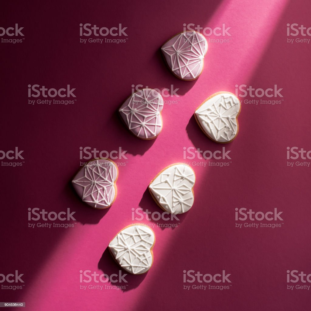 top view of glazed heart shaped cookies on pink tabletop stock photo