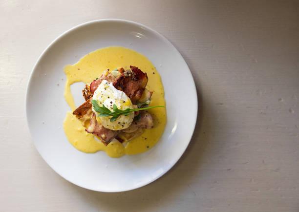 draufsicht der gourmet-eggs benedict mit speck - sauce hollandaise stock-fotos und bilder
