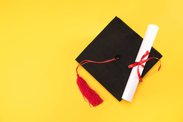 top view of graduation mortarboard and diploma on yellow background, education concept - diploma stock photos and pictures