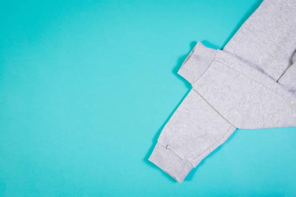 draufsicht der graue jogginghose auf türkisfarbenen pastelltönen hintergrund. - sweatpants stock-fotos und bilder