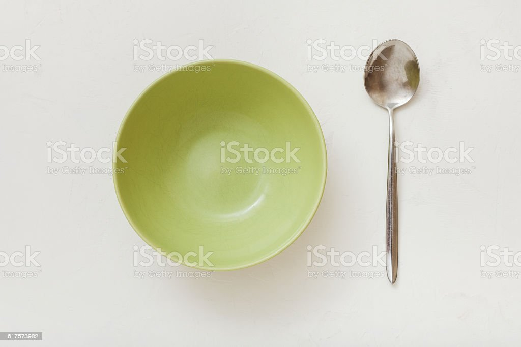top view of green bowl and spoon on white plaster stock photo