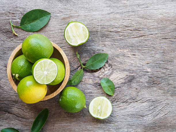 Top view of green lemon group and slice in bowl stock photo