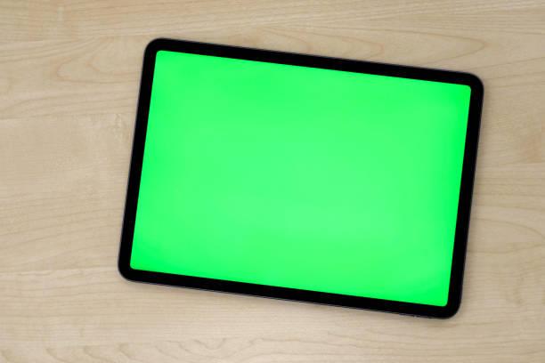 bovenaanzicht van groen scherm tablet-apparaat op patroon houten tafel - green screen stockfoto's en -beelden