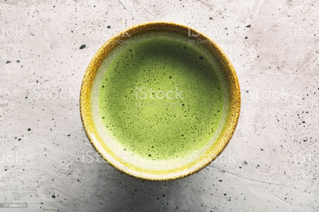 Top view of green tea matcha in a bowl on concrete surface. It is a...
