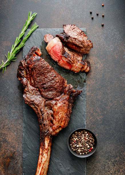top view of grilled beef steak tomahawk with spices on a black slate. flat lay, dinner concept. - raw steak imagens e fotografias de stock