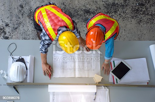 istock Top view of group of engineering team is meeting, planning construction work,looking paper plans at construction site,overhead view 902898076