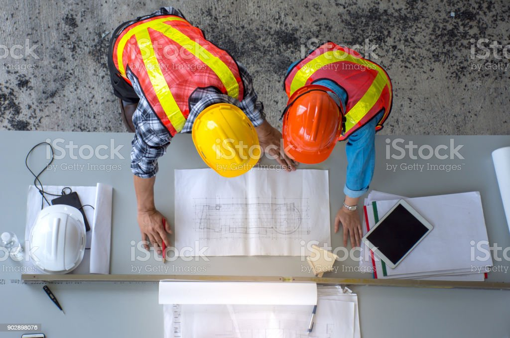 Top view of group of engineering team is meeting, planning construction work,looking paper plans at construction site,overhead view stock photo