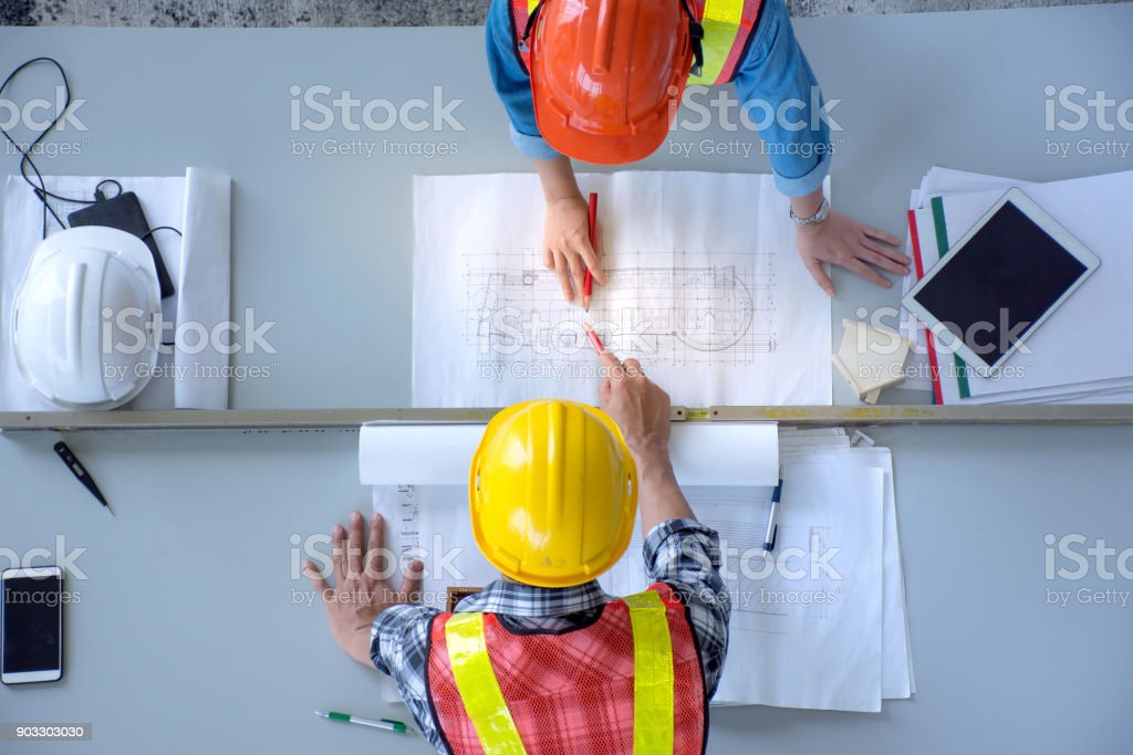 Top view of group of engineering team is meeting, planning construction work,looking paper plans at construction site,overhead view royalty-free stock photo