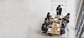 istock Top view of group of multiethnic people meeting in an office, Aerial view with businessman and businesswoman sitting around a conference table and capping for celebrate winner teamwork star award 1222164326