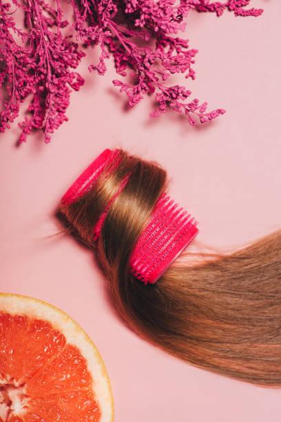 draufsicht des haares rollte lockenwickler mit blumen und orange auf rosa oberfläche - orangenscheiben trocknen stock-fotos und bilder
