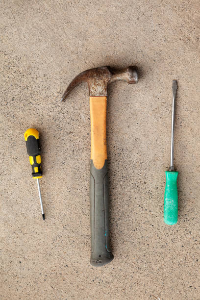 Top view of hammer and screw drivers on concrete background, flat lay of working tools stock photo