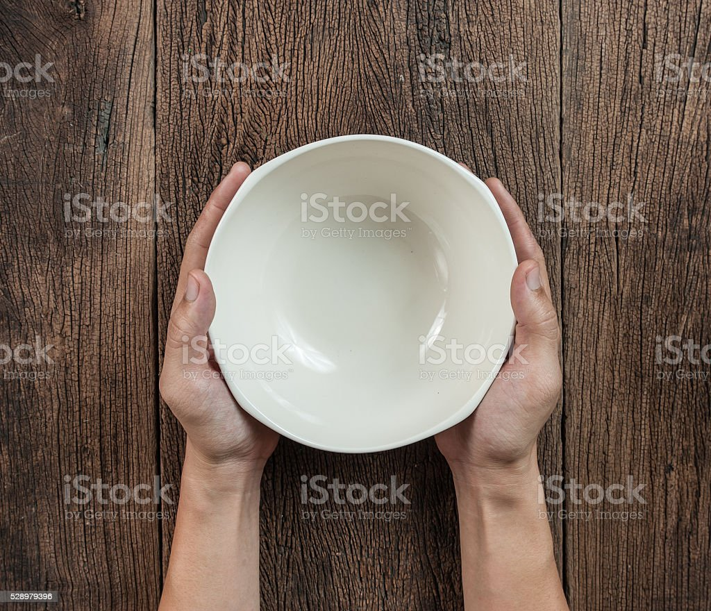 Top view of hand hold a empty bowl on wood stock photo