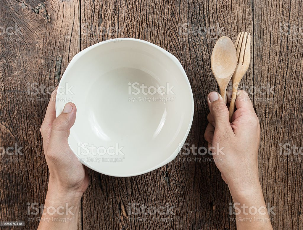 Top view of hand hold a empty bowl with spoon stock photo
