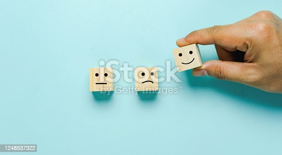 Top view of  Hand holding of Happy icon on cube blocks about rating feedback of survey from customer. Business annual survey concept. Many sad or happily on wooden on blue paper.
