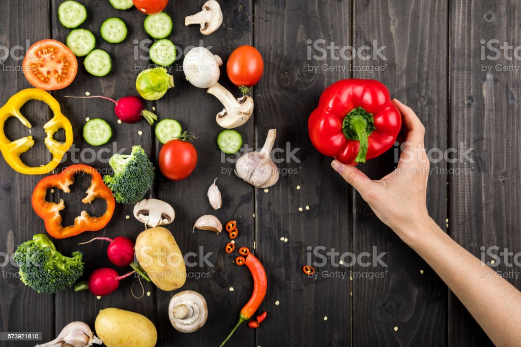 Top view of hand holding pepper and fresh vegetables on wooden table background photo libre de droits