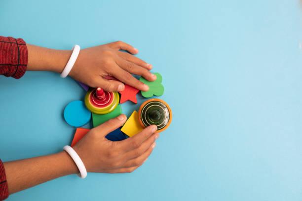 top-ansicht von hand eines kinder greifen bunte holzbausteine mit verschiedenen formen für das spielen von kindern auf blauem hintergrund. - autismus stock-fotos und bilder
