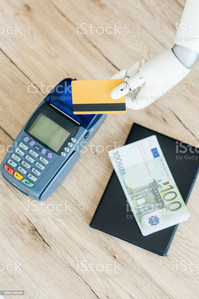 top view of hand of robot holding credit card above payment terminal and money on wooden table zbiór zdjęć royalty-free