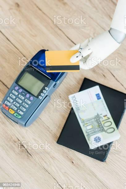 Widok Z Góry Na Rękę Robota Trzymającego Kartę Kredytową Nad Terminalem Płatniczym I Pieniądze Na Drewnianym Stole - zdjęcia stockowe i więcej obrazów Banknot