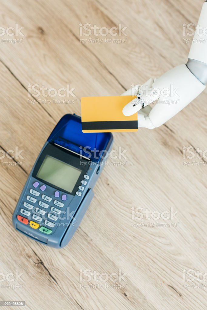 top view of hand of robot holding credit card above payment terminal on wooden table zbiór zdjęć royalty-free