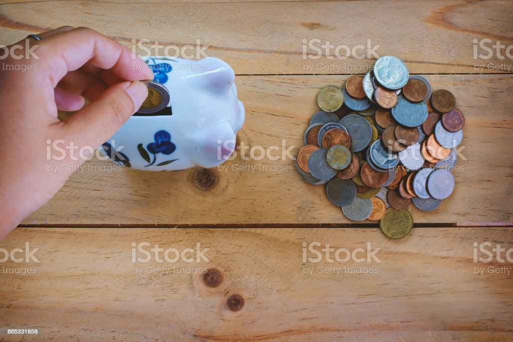 Top view of hand saving coin to piggy bank and a pile of Thai baht coins on wooden table for business and finance concept stock photo