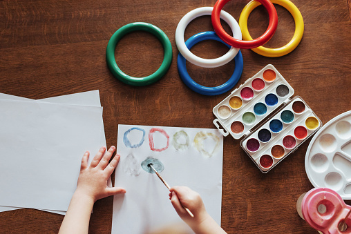 636761588 istock photo Top view of hands and brush paint watercolor  gouache 645343628