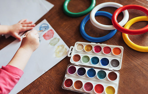 636761588 istock photo Top view of hands and brush paint watercolor  gouache 645343740