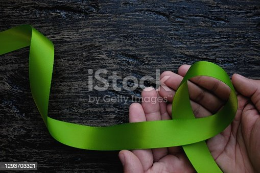 Top view of hands holding lime green color ribbon on dark background. Non-hodgkin lymphoma cancer, lyme disease, muscular dystrophy and postpartum depression awareness concept