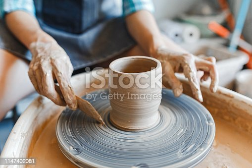 istock Top view of hands with clay making of a ceramic pot on the pottery wheel, hobby and leisure with pleasure concept 1147402081