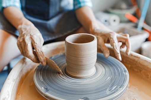 Top view of hands with clay making of a ceramic pot on the pottery wheel, hobby and leisure with pleasure concept