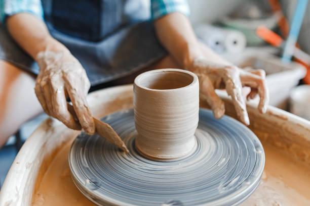Blick auf die Hände mit der Tonherstellung eines Keramiktopfes auf dem Töpferrad, Hobby und Freizeit mit Genusskonzept – Foto