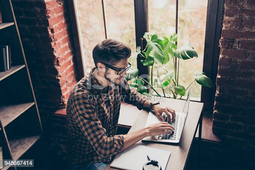 932763106 istock photo Top view of handsome  young man in glasses typing on laptop 948667414