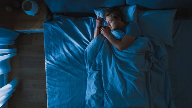 Top Blick auf den schönen jungen Mann, der cozily auf einem Bett in seinem Schlafzimmer bei Nacht schläft. Blaue nächtliche Farben mit kalten schwachen Laternenpfosten Licht leuchtet durch das Fenster. – Foto