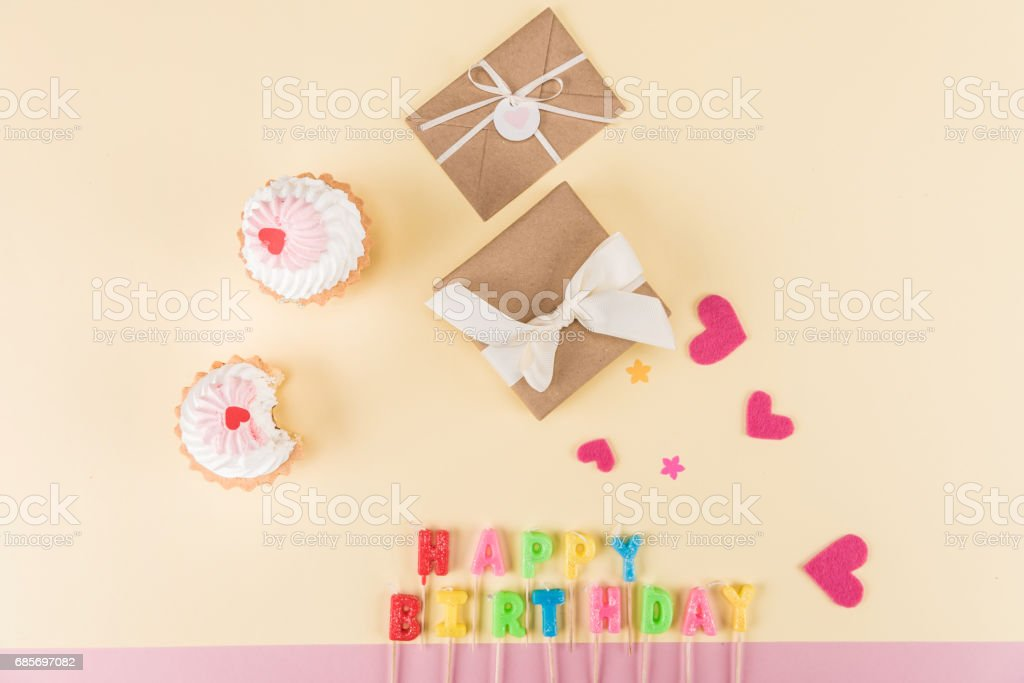 Top view of happy birthday lettering, envelopes with ribbons and hearts symbols on pink, birthday party concept Lizenzfreies stock-foto