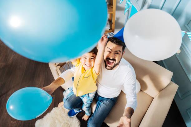 draufsicht der glückliche vater und sohn spaß mit ballons - einladungskarten kindergeburtstag stock-fotos und bilder